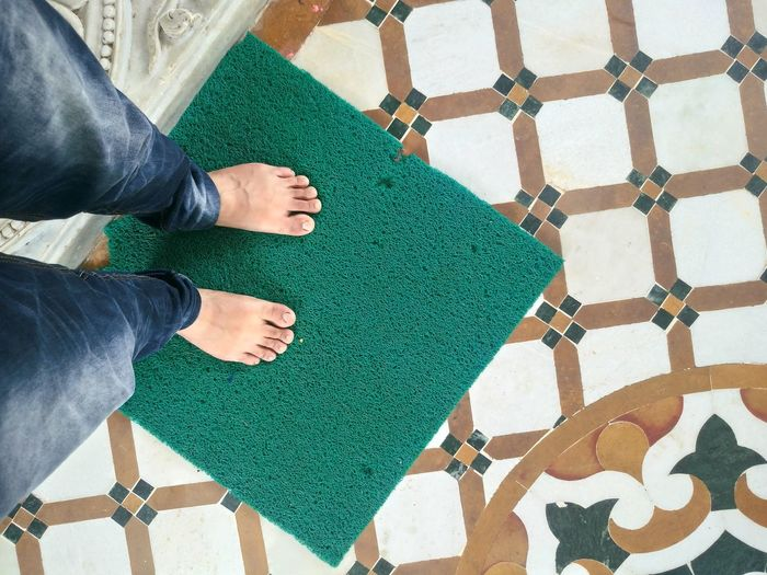 Low section of man standing on doormat in temple