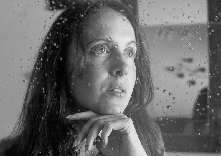 Portrait of woman looking through wet window in rainy season