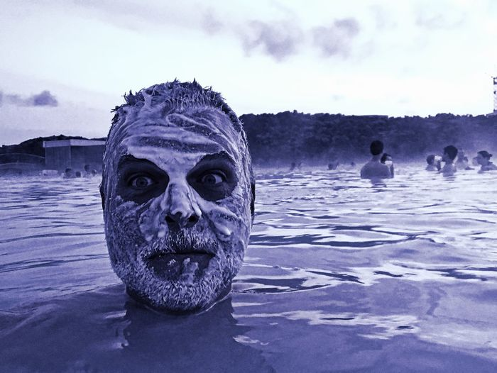 Close-up of man with white mud on face swimming in lagoon