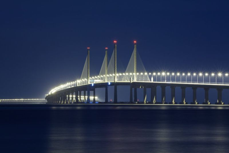 Illuminated penang bridge over strait of malacca against clear sky at night