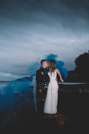 Full length of couple kissing on the mouth while standing amidst smoke against sky