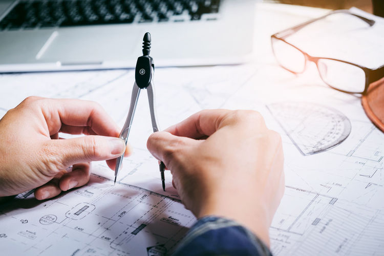Cropped hands of person holding drawing compass on desk