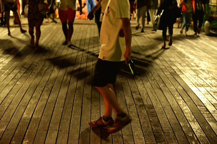 Low section of people walking on deck at night