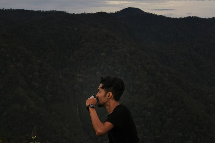 Side View Of Man Drinking Against Mountains At Dusk