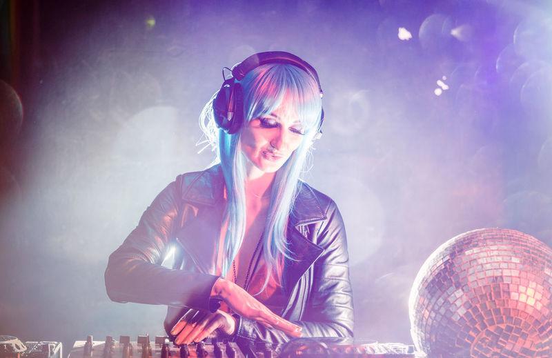Woman playing dj at music concert
