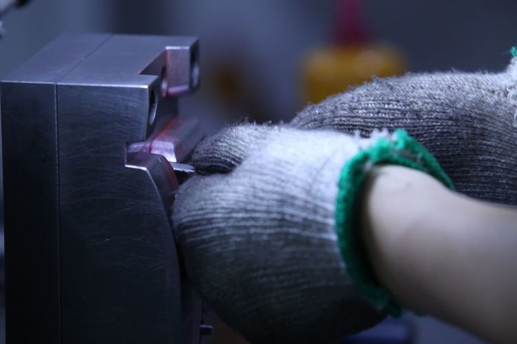 Cropped hands wearing gloves holding equipment