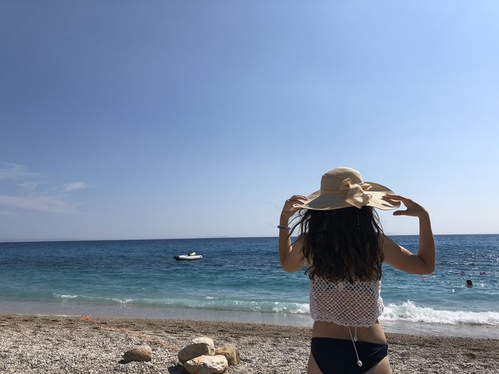 Rear view of woman wearing hat while standing at beach against sky