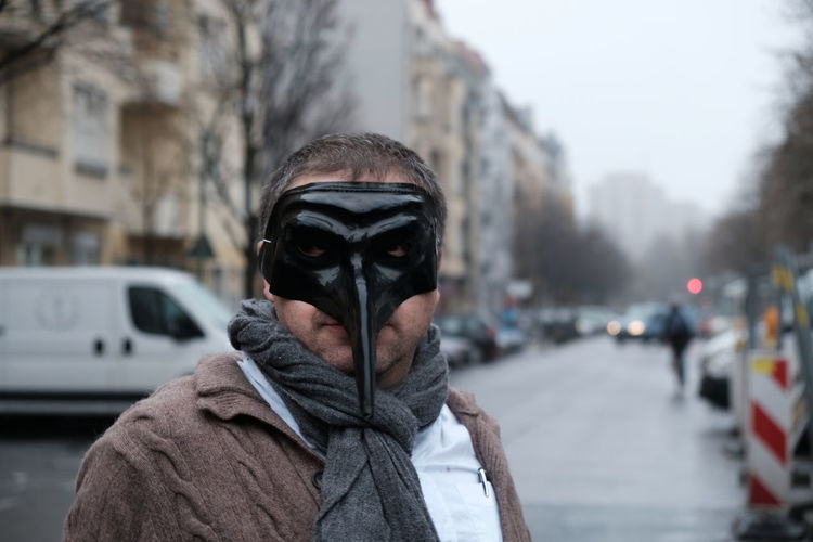 Portrait of man wearing mask on street in city