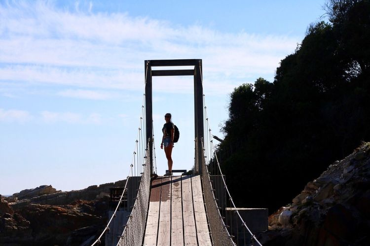 Full length of woman standing on rope bridge against sky