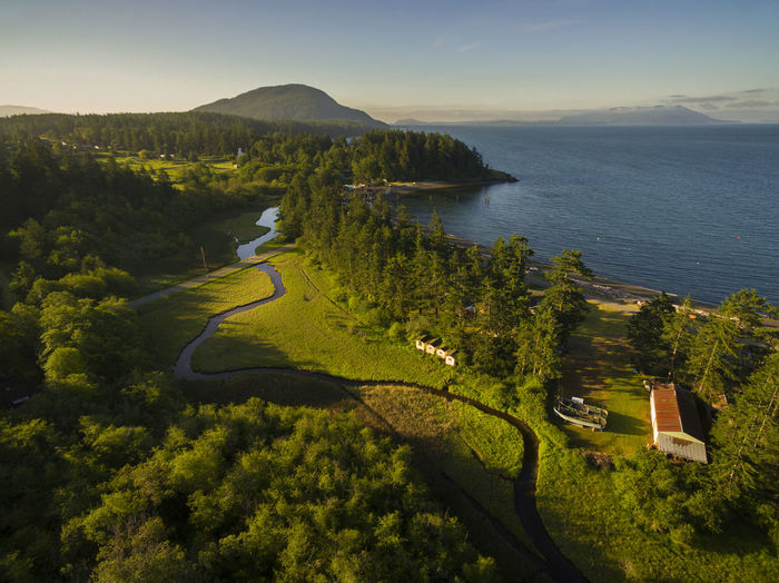 Legoe Bay, Lummi Island, Washington. The west coast of Lummi Island. Two reefnet boats can be seen in the lower right hand corner in the field. The Lummi Island Congregational Church is in the upper left. The slough meanders parallel to Legoe Bay on the right. Beauty In Nature Church High Angle View Landscape Lummi Island Mountain Nature Nature No People Outdoors Rural Scene Salish Sea San Juan Islands Scenics Slough Sunrise Tranquil Scene Travel Destinations Tree Washington Washington State Water Wetland Whatcom County Willows Inn