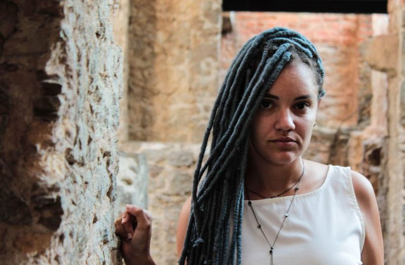 Portrait of woman with dreadlocks against wall