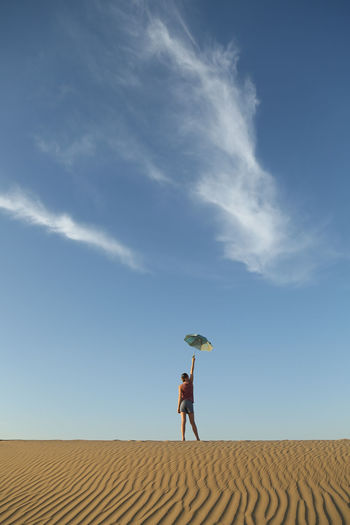 Full length of woman standing on desert against sky