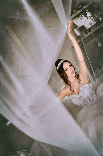 High angle portrait of beautiful bride holding curtain