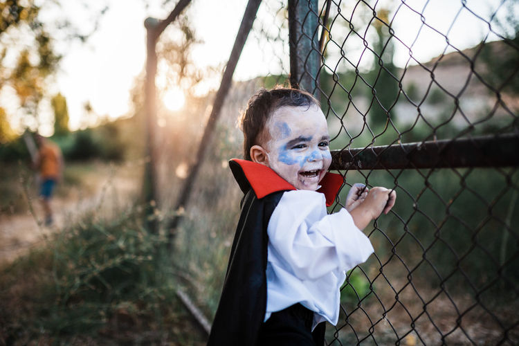 Portrait of boy standing by chainlink fence on field