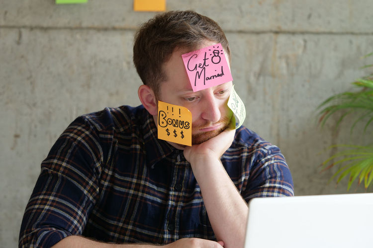 Architect with adhesive notes on face in office
