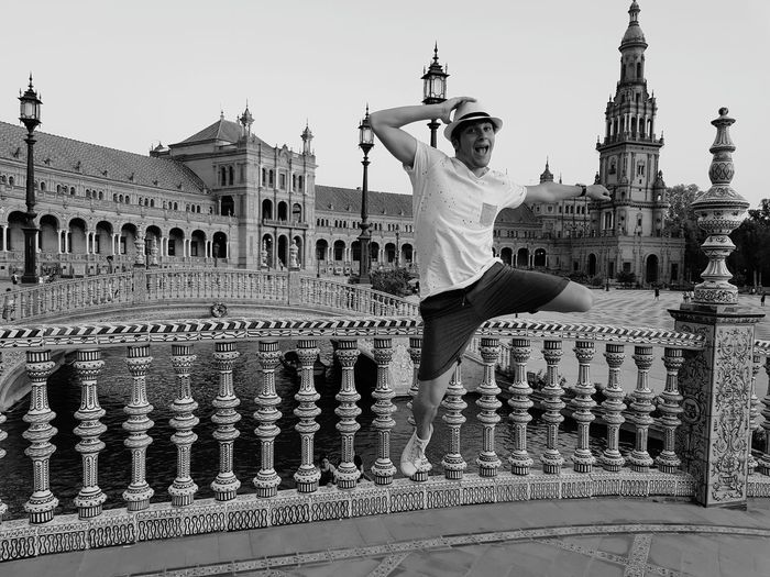 Portrait Of Cheerful Young Man Jumping In City