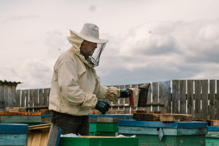 Beekeeper in a protective suit fumigates hives