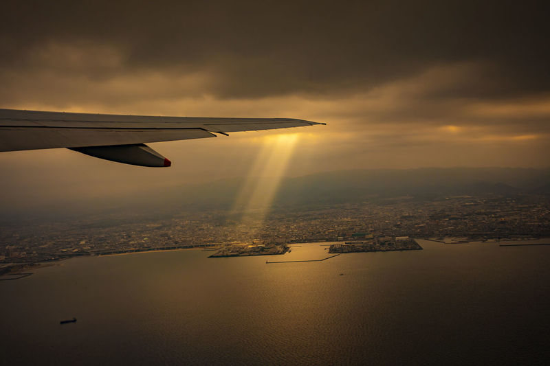 view from plane window of sunlight ray over osaka city harbor Sky Airplane Flying Cloud - Sky Mode Of Transportation Aircraft Wing Cityscape Water Aerial View Sunset Mid-air Outdoors Sun Light Ray Sunbeam Skies Wing UFO UFO? Amazing Atmosphere Awe Aircraft Plane