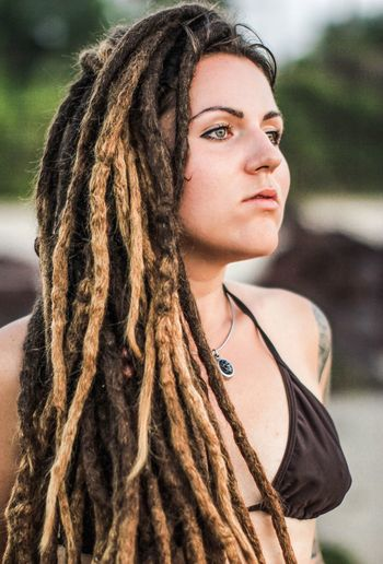 Young woman with dreadlocks looking away