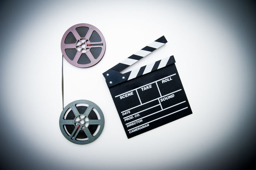 Movie clapper board and super 8 film reels Archival Arts Culture And Entertainment Cinema Clapper Clapperboard Colored Background Film Industry Film Reel Filmstrips Industry MOVIE No People Studio Shot Super 8 White Background