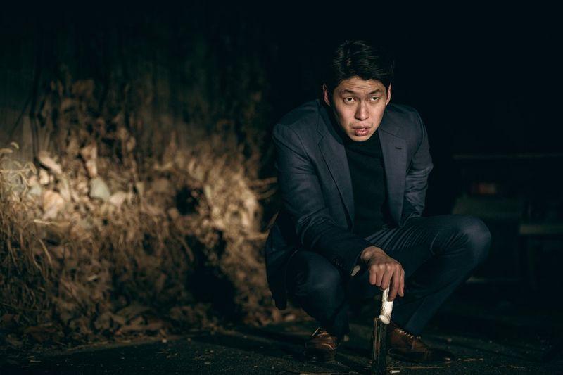 Man holding knife while crouching on land at night