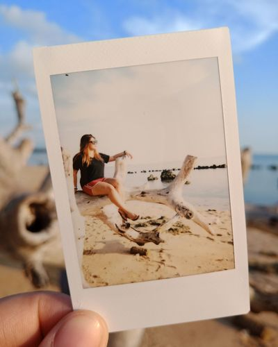 Cropped Hand Of Woman Holding Instant Print Transfer At Beach Against Sky