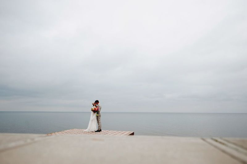 Bride And Bridegroom Standing On Pier In Sea During Wedding Ceremony