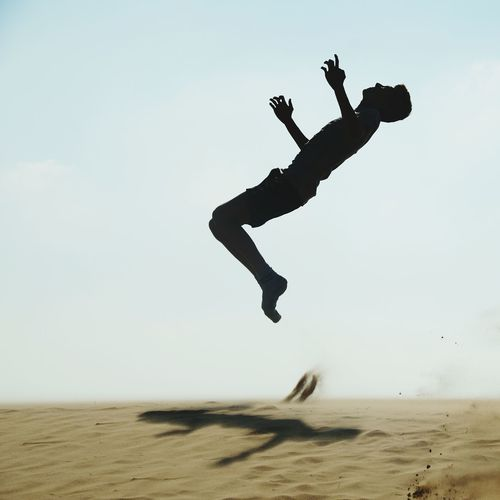 Silhouette mid adult man jumping on sand at beach against clear sky