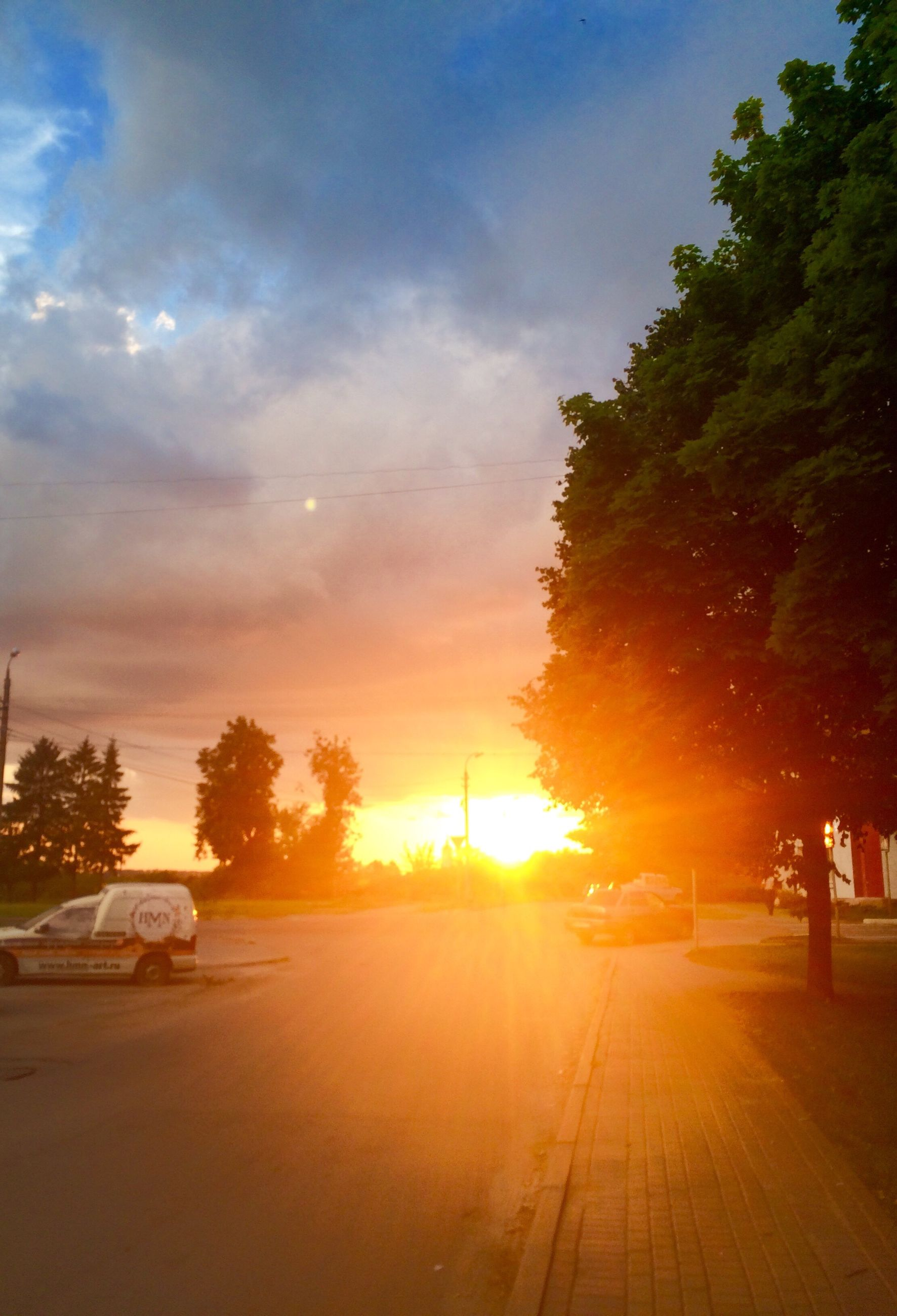 transportation, tree, car, land vehicle, sunset, mode of transport, road, sun, street, lens flare, sunbeam, sunlight, orange color, sky, tranquil scene, outdoors, vehicle, scenics, tranquility, parked, beauty in nature, cloud - sky, the way forward, dramatic sky