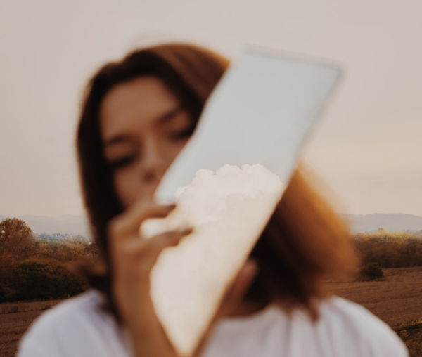 Close-Up Of Woman Holding Mirror Against Sky
