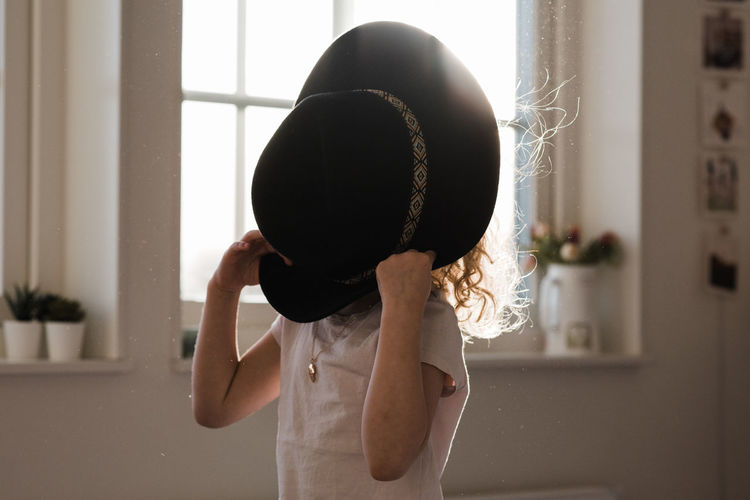 Midsection of woman holding hat at home