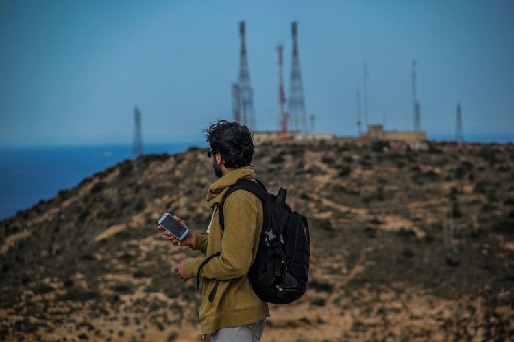 Rear view of man using mobile phone against clear sky
