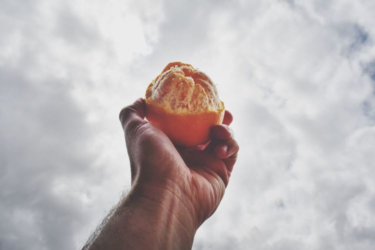 Cropped image of hand holding ice cream against sky