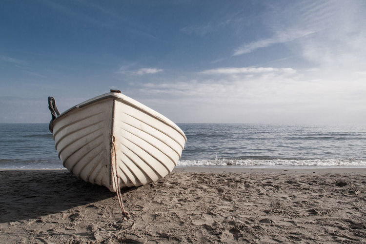 Boat Moored At Beach Against Sky On Sunny Day
