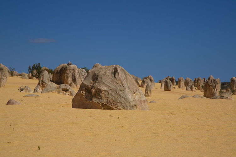Panoramic view of desert against clear blue sky