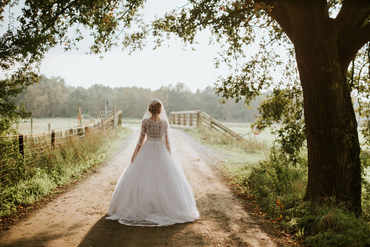 Rear view of bride walking on footpath