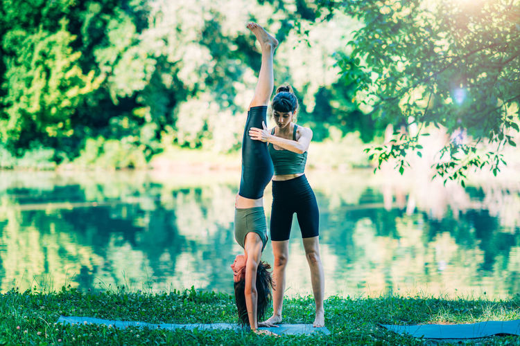 Women doing yoga by the water. instructor helping woman to do headstand.
