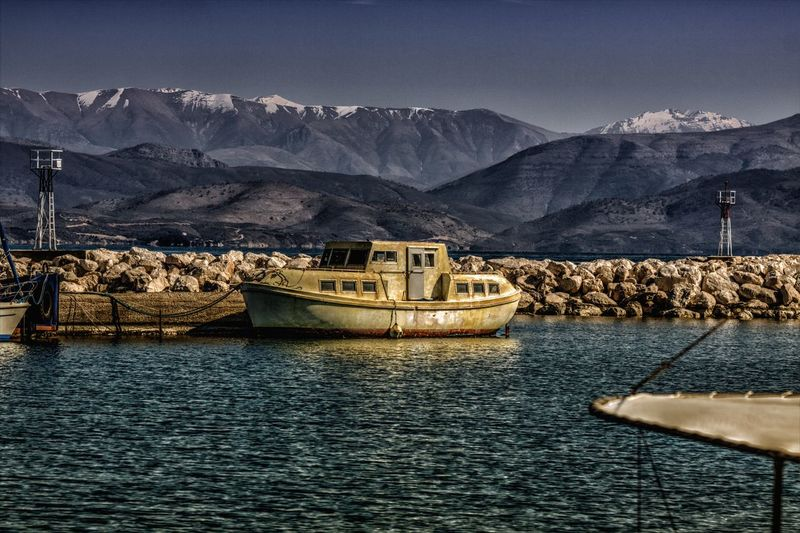 Small boat with snow-capped mountain tops at the back. Mountain Water Transportation Mode Of Transportation Mountain Range Nautical Vessel Sky Beauty In Nature Scenics - Nature Nature Waterfront Sea No People Tranquil Scene Tranquility Day Travel Non-urban Scene Outdoors Formation Boat Boats Port Snow Snowcapped Mountain