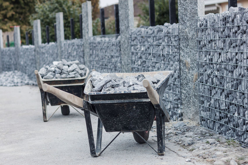 wheelbarrows loaded with gravel in front of gabion wall Construction Construction Site Industry Natural Wall Wheelbarrow Work Full Gabion Gabion Wall Garden Garden Design Gravel Horticulture Loaded No People Outdoors Stone Stone Wall Work Tool