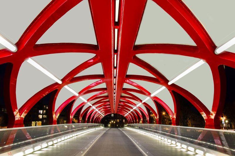 Empty illuminated modern footbridge in city at night