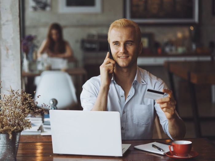 Smiling man holding credit card while talking on phone