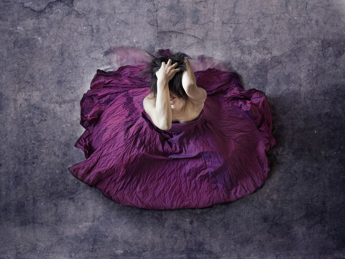 High angle view of depressed woman with hands in hair wearing purple dress while sitting on floor