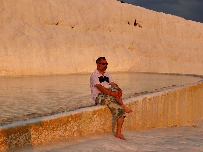 Mature man sitting by travertine pool at pamukkale