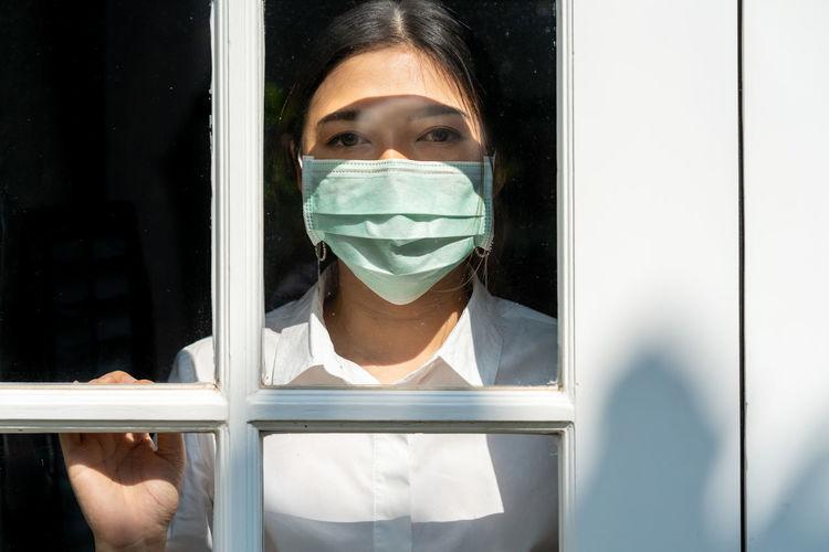 Portrait of woman wearing mask seen through window