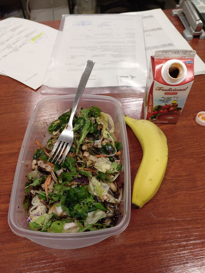 Having my launch at work Banana Drink Food Food And Drink Fork Freshness Gaspacho Healthy Eating High Angle View Indoors  Launch Launch Break Launch Time Papers Salad Table Tetrabrick Tupperware Vegetable