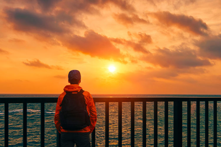 Man Standing By Railing Against Sea During Sunset
