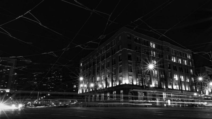 Illuminated street against sky in city at night