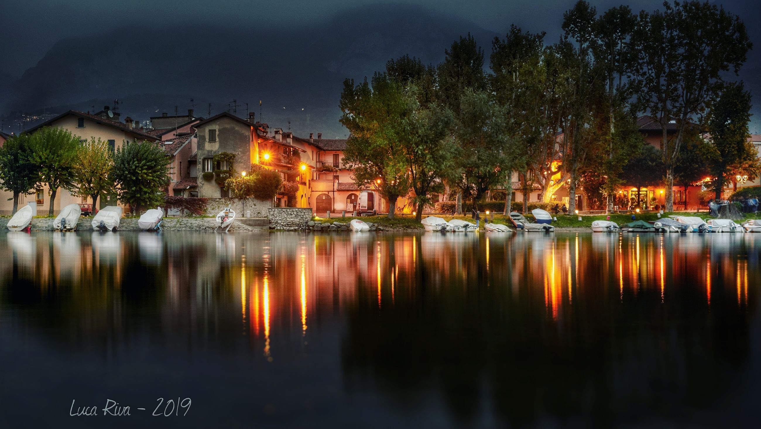 reflection, illuminated, building exterior, water, built structure, tree, architecture, building, waterfront, lake, plant, no people, house, nature, night, residential district, sky, dusk, outdoors