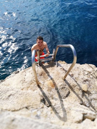 High angle view of shirtless man climbing ladder against sea