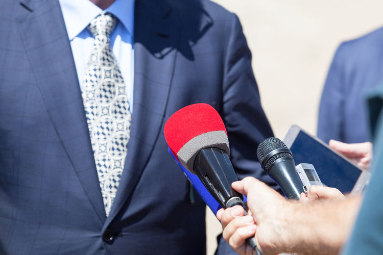 An unrecognizable politician or businessman giving statement to the media. Reporters interviewing a public figure. Business Well-dressed Journalist Microphone Suit Politician The Media Businessman Politics Business Person Interview Press Media Interviewing Journalism Reporting Reporter Statement Public Relations Publicimage Publicity Speak Out Communication Information Broadcasting